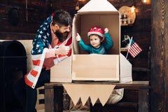 Sen o karierze kosmonauta Ojciec i mała chłopiec w papierze podskakujemy z flaga amerykańską Szczęśliwy dzień niepodległości zdjęcia stock