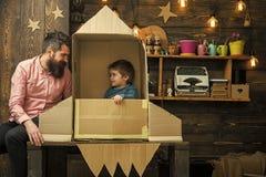 Sen przestrzeń Dzieciak szczęśliwy siedzi w kartonowej ręcznie robiony rakiecie Chłopiec sztuka z tata, ojciec, mały kosmonauta s obraz royalty free