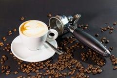 Sena kopp och bönor för kaffe på en svart bakgrund Arkivbild