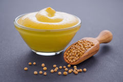 Senape fresca in ciotola di vetro e mestolo di legno con i semi di senape su fondo scuro, horisontal Fotografia Stock