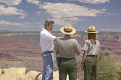 Senator John Kerry speaking with 2 rangers at rim of Bright Angel Lookout, Grand Canyon, AZ Stock Photos