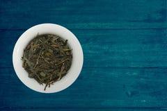 Sencha japonês do chá verde no apresentador no fundo de madeira rústico azul Foto de Stock Royalty Free