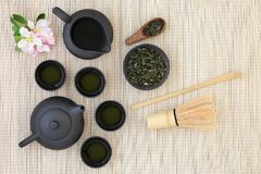 Sencha Sukiygu Makoto Japanese Tea. With teapot and cups, dried leaves, whisk, stick stirrer and spring blossom on bamboo background royalty free stock image