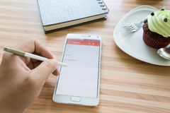 Send E mail at phone in coffee shop Stock Photography