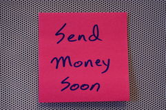 Send money. Hand written message on pink sticky note with black and white back ground stock photo