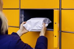 Free Send Or Receive Parcel With Self Service Post Terminal Machine. Hand With Package Stock Photos - 206682923
