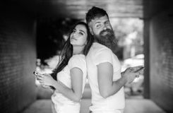 Send provocative message. Couple ignore real communication. Couple chatting smartphones. Girl and bearded man stand back. Send provocative message. Couple ignore royalty free stock image