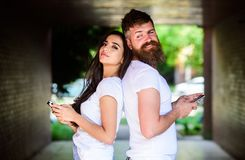 Send provocative message. Couple ignore real communication. Couple chatting smartphones. Girl and bearded man stand back. Send provocative message. Couple ignore stock photography