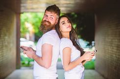 Send provocative message. Couple ignore real communication. Couple chatting smartphones. Girl and bearded man stand back. Send provocative message. Couple ignore stock photo