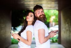 Send provocative message. Virtual cheating online. Couple ignore real communication. Couple chatting smartphones. Girl. And bearded men stand back to back porch royalty free stock image