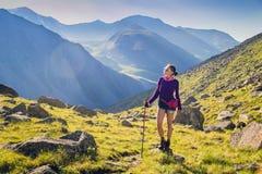 Senderismo de la mujer en las montañas Fotos de archivo libres de regalías