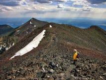 Senderismo del caminante a lo largo de la alta montaña con el cielo dramático en distancia Fotografía de archivo