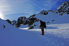 Senderismo del escalador a través de la nieve Fotografía de archivo