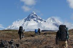 Senderismo del grupo de los caminantes en montaña en el fondo de volcanes Imagen de archivo