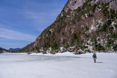 Senderismo del hombre a través de un lago congelado Imagenes de archivo