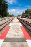 Sendero de la tira del rojo y del blanco entre el ferrocarril Foto de archivo