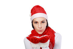 Sending blow kiss. People, holidays, christmas and celebration concept - beautiful  woman in santa hat and red dress sending blow kiss Royalty Free Stock Photography