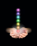 Sending chakra healing energy. Hands emerging from darkness, cupped with seven charka vortexes floating above Royalty Free Stock Photo