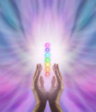Sending Chakra Healing Energy. Male parallel hands facing upwards with white energy and the Seven Chakras floating between on a pink and blue ethereal energy Stock Photography