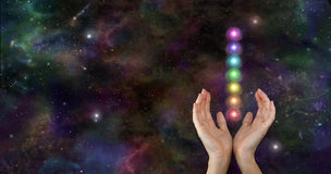 Sending chakra healing energy through space. Female hands reaching upwards with the seven chakras floating between, on a dark deep space night sky background Royalty Free Stock Photography