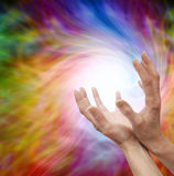 Sending Distant Healing Energy. Female healer's outstretched cupped hands on colorful vortex swirling energy background Stock Photo