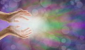 Sending distant healing. Female hands reaching out with white light and bokeh effect background Royalty Free Stock Images