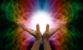 Sending Distant Healing. Healer's outstretched open hands with ball of white light between on a rainbow colored web-like energy formation background Stock Image