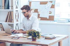 Sending email to his coworkers. Side view of handsome young man in glasses working with laptop while sitting at his working place Royalty Free Stock Image