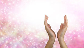 Sending Healing Energy. Female healing hands reaching up from a pink sparkling energy background royalty free stock photography