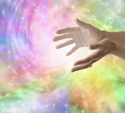 Sending Healing Energy. Female healer with hands out stretched sending healing energy with a bright sparkling colorful vortex background Stock Images