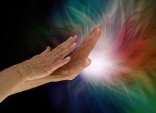 Sending light and healing energy out where it is needed. Female healers hands appearing to push out white light from the palm with darkness on left and multiple stock photo