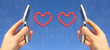 Sending Love. Two hands hold up two mobile phones in the air with two hearts between them Stock Image