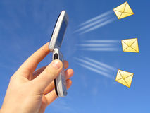Sending a Message. Hand holding cell phone with icons of mail spraying out from it.  Could be receiving or sending messages or email Royalty Free Stock Photo