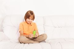 Sending messages. Little Caucasian boy with amazing big smile  text her friends on social network, looking at screen sitting on the coach in living room Stock Photography