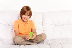 Sending messages with mobile phone. Little Caucasian boy with amazing big smile  SMS her friends sitting on the coach in living room Stock Photo