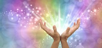 Sending out beautiful powerful white light healing energy. Pair of open hands facing up with white energy beaming outwards against a sparkling rainbow coloured stock photos