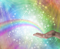 Sending Rainbow Healing Energy. Male hand palm up with a rainbow appearing to end in his palm on a rainbow colored background with glittering sparkles and Stock Image