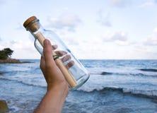 Sending s.o.s. Hand throwing s.o.s. in a bottle Stock Photos