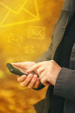 Sending SMS messages on mobile phone in autumn Royalty Free Stock Photos