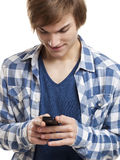 Sending text messages. Portrait of handsome young man sending text messages with is mobile phone, isolated on white background Stock Photography