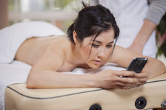 Sending a text at a spa Stock Photography