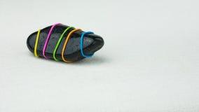Sendo uma pedra preta diferente com as listras coloridas no fundo brilhante fotografia de stock