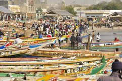 Senegal fish market. On the beach in Dakar, Soumbedioune, marche aux poissons, with colorful piroques and fishermans Stock Images