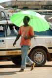 SENEGAL - 12. JUNI: Ein Mann, der in die Straße mit einem Regenschirm geht Lizenzfreies Stockfoto