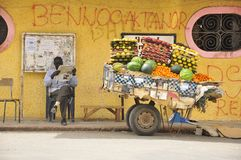 Senegal street vendor. Senegal fruit street vendor reading newspaper, african colors. Saint Louis street life Royalty Free Stock Photo