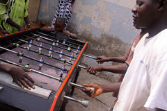 Senegalese Boys Play Foosball. A group of boys in Dakar, Senegal, play foosball on the sidewalk as part of their Tabaski holiday (Muslim festival of Eid-al-Adha Royalty Free Stock Image
