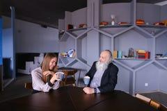 Senescent человек встречал с женским работником для чашки чаю во время bre Стоковые Изображения RF