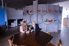 Senescent человек встречал с женским работником для чашки чаю во время bre Стоковые Фотографии RF