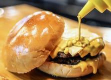 Senfsoße zusammengedrückt auf Hamburger lizenzfreies stockfoto