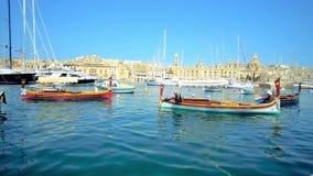 SENGLEA, ΜΑΛΤΑ - 19 ΙΟΥΝΊΟΥ 2018: Φυσικές βάρκες luzzu, που λικνίζουν στα ευγενή κύματα στη μαρίνα Vittoriosa με μια άποψη σχετικ φιλμ μικρού μήκους